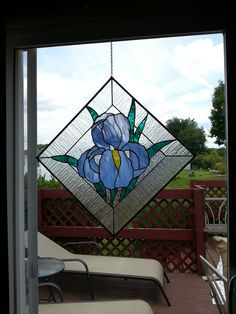 Blue Iris stained glass panel was created by me using the Tiffany method of copper foiling and solder. This piece contains blue, yellow and green