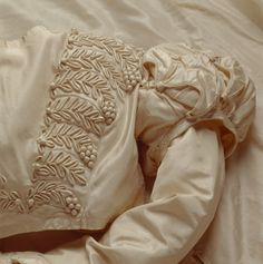 Detail of wedding gown worn by Mary Elizabeth Williams on the event of her marriage to George Hammond Lucy, 2 Dec 1823. National Trust, Killerton. White silk with applied vine leaves and grape bunches on bodice.