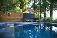 Perfect pergola next to the pool- clean lines, dark blue water and dark orangey colored wood.