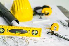 Планы строительства с шлемом и чертежными инструментами на чертежах. Бесплатные Фотографии