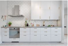 Contemporary white kitchen given a salvage edge with white brick tiling and blonde wood accessories