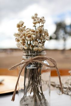 Dried flowers on mason jars. Perfect for winter wedding when fresh flowers are out of season. They're also very cheap.