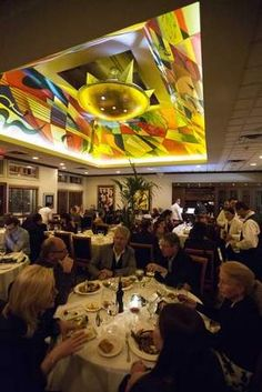 A brightly colored mural decorates the all-white dining room at Bacco Ristorante in Southfield.