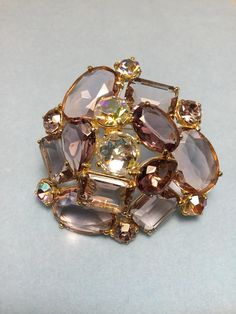 Absolutely gorgeous Schiaparelli brooch done on brilliant gold tone metal. Starting in the center is a rosette cut AB cabachon with a lavender openback rectangle emerald cut a openback lavender pear, and a smaller pear and a oval faceted laveneder openback. One large golden AB chaton. The