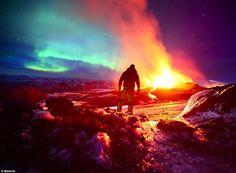 Northern lights over erupting volcano.
