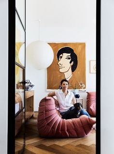 "Rachel cuddles up with Sydney Sausage on her [Ligne Roset](https://www.ligne-roset.com/au/) ""Togo"" sofa. A large paper shade lights up an original Bernard Villemot portrait from [Vintage Posters Only](https://www.vintagepostersonly.com/)."