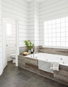 Shiplap walls, distressed-wood cabinets, and mixed metal finishes set a new tone for a master bath in desperate need of a warmer, less generic look Tile Around Bathtub, Bathtub Tile Surround, Wood Paneling Makeover, Master Tub, Master Bathroom, Wood Tub, Bathtub Decor, Corner Tub, Tub Remodel