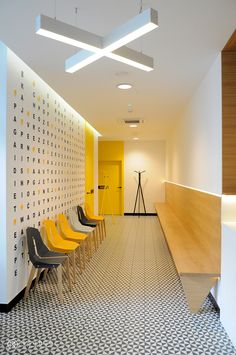 I LIKE THE PLAYFULNESS OF THE LETTERS BEHIND THE SEATING & THE TILE FLOORS & POPS OF BRIGHT COLOR dental clinic by makastudio.pl