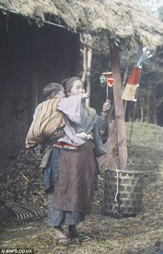 A country woman successfully entertains a child with a handmade toy.  Hand-colored photo, 1910, Japan.  Photography  by Tamamura Kozaburo