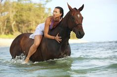 horse riding next to ocean