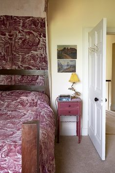 This spare room in the restored Cumbrian farmhouse of Annabel Lewis (owner of V V Rouleaux) has an antique canopied bed covered in toile de Jouy, with a nightstand painted in a matching hue.