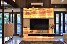 The use of exotic backlit onyx in the TV unit gives luxurious and rich look, complimented with a floral jali pattern, roles a red carpet for guest in the modern living area by A.J Architects. Luxury Interior, Interior Design, Gated Community, Common Area, Tv Unit, Large Windows, Teak Wood, Second Floor, Ground Floor