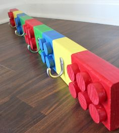 Your little one will love this adorable coat rack that looks like giant Legos! Learn how to make one using wooden dowels from DIY On The Cheap. || @Erin B @ DIY On the Cheap