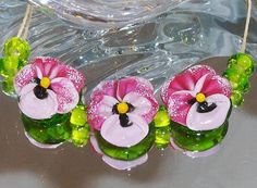 A pretty set of 3 pink pansie beads. Each pansy has been dusted with white enamels on 4 of the petals. The pansys have been made on a base of transparent green glass in the lental shape. The spacers are also transparent green. Pansies measure 20mm   Spacers measure 8mm. Thank you for looking today.