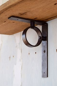 Hand-hammered metal shelf bracket with blackened iron finish. Connected with hammered rivets for an industrial look. This shelf bracket measures 9 1/2 inches heigh by 1 1/2 inches wide and 7 inches from the wall. We recommend a shelf bracket every 36 inches. These brackets are very strong and will hold heavy items such as pots, pans, and dish-ware when installed properly. All our brackets are made to order. Please allow approximately 2 to 3 weeks for delivery. Brackets sold separately…