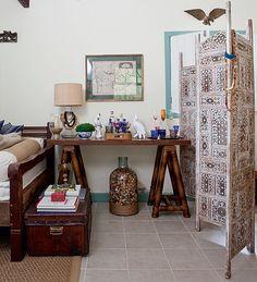 Aparador com pés de cavaletes feitos de bambu. No projeto, o móvel serve como criado-mudo e bar.