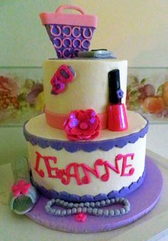Coach purse, cell phone perched on top, nail polish and over-sized hair flower in the center, heels and pearls at the bottom.  All fondant.