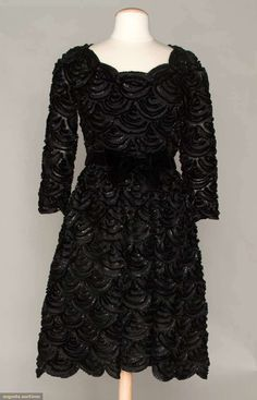 Christian Dior Couture Black Dinner Dress 1964. All over scallop pattern of alternating silk braid & thick eyelash fringe, ballet neckline, 3/4 sleeves, boned midriff band, black velvet belt w/ bow, horsehair reinforced hem and stiffened organza petticoat.
