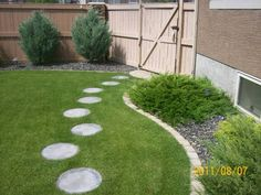 These round stepping stones lead to the back patio area. Placing them with the right spacing and offsetting them, is the key achieving the right look even with a manufactured product.
