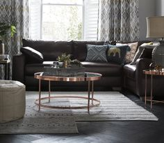 Image of a lounge, with a round copper table, dark brown leather corner sofa and tribal print cushions and curtains.