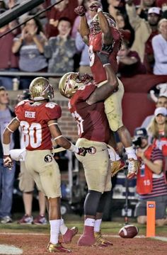 Florida State running back Devonta Freeman (8) gets listed off the ground by offensive linesman Bobby Hart (51) after scoring a touchdown. Also celebrating is wide receiver Rashad Greene (80). (Chris O'Meara/AP)