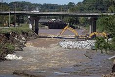 Crews work Wednesday to add rocks and sandbags to the breached Columbia Canal. Water continued to flow from the canal Wednesday behind the South Carolina State Museum.