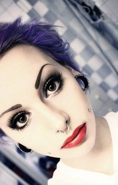 septum piercing and jewelled tunnels.