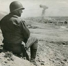 Patton watching tanks battle in Tunisia.