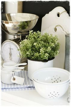 Kitchen vignette with vintage scale, plant, measuring cups, strainer.