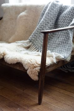 Sheepskins thrown over a vintage chair or sofa seem to be all the rage. I rather like it and it could conveniently hide a chair in need of reupholstery