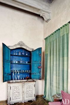In a Rome living room, an antique Italian painted cabinet is filled with glassware.
