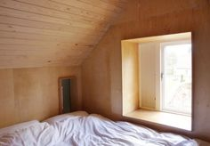 Wood-paneled modern farmhouse bedroom in the Thursford Barn by Lynch Architects | Remodelista