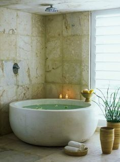 Round bath tub and shower head in the ceiling (so cute - looks like a big soup bowl!)