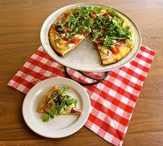 The Central West End – mozzarella, volpi prosciutto, goat cheese, cherry tomatoes, red onions & arugula.