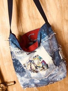 This delightful tote is the perfect size with two inside pockets and one on the outside. Has a navy canvas shoulder strap 30. Very scrappy and frayed so fun and funky denim and lots of patches. Wood button closure. Measurments: 14 1/2 wide 12 deep 5 flat bottom