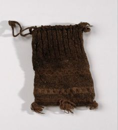 This knitted woollen purse was discovered on a man's body found at Gunnister in Northmavine in Shetland in the late 17th century. When he died, the man was wearing a coat, jacket, shirt, breeches, cap and stockings. The purse has three bands of decorative Fair Isle pattern on the main body. There are draw strings at the top and three tassels at the bottom.
