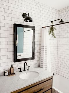 A bathroom has white subway tile and dark grout. A black-and-walnut vanity has black drawer pulls. The medicine cabinet, faucet, light fixture, and shower head are black. Bad Inspiration, Bathroom Inspiration, Bathroom Ideas, Budget Bathroom, Bathroom Shelves, Bathroom Light Fixtures, Bathroom Lighting, Vanity Lighting, Subway Tile Showers