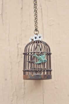 Add some whimsy to your wardrobe with this vintage inspired necklace. An adorable birdcage with an aged patina is paired with a sweet little verdigris swallow and 3 vintage enameled metal flowers. Hung from an antiqued brass 26 chain. Length of chain can be adjusted upon request.