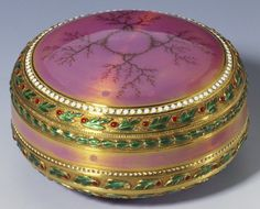 Circular gold box and cover tapering to top and bottom with straight sides. Cover enamelled with simulated moss agate on pink guilloché ground. Around borders red and green enamelled leaves and imitation half pearls.    Mark of Michael Perchin; FABERGÉ in Cyrillic; gold mark of 72 zolotniks (before 1896)