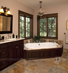 Traditional cabinetry in the master bath with a corner tub. Ceramic tile floor.