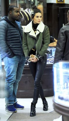 In an olive shearling jacket, black Palm Angels turtleneck, gold medallion necklace, leather pants and patent leather ankle boots while shopping in New York City.