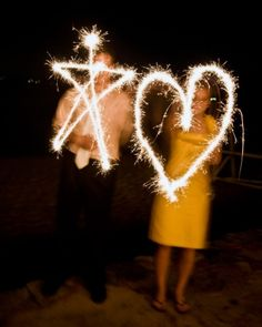 Wedding guests trace shapes in the air with a couple of blazing sparklers