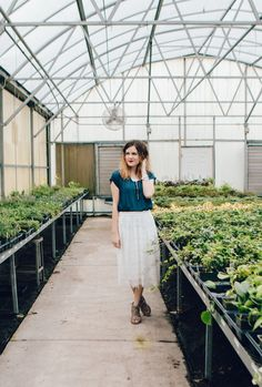 Let's Share a Little More Self Love, greenhouse photos, greenhouse, greenhouse photoshoot, spring skirt outfit, spring modest skirt, modest outfit, modest skirt, teacher outfit, teacher fashion, white lace skirt, navy blue top, navy blue blouse, wedge heels, naturally curly hair, red lips, self love, lifestyle blog, fashion blog