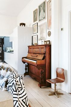 In the kitchen-living area, a picture gallery featuring styles and cultures of the world hangs above a Rubenstein piano. Milton House, Piano, Music Decor, Built In Bench, Dining Nook, Elegant Homes, One Bedroom, Decor Interior Design, Living Area
