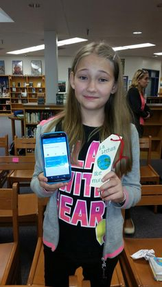 A student shows a bookmark with a message in Spanish and the translation on the phone. Photo submitted by Dedra Van Gelker- School Libraries Make a Difference