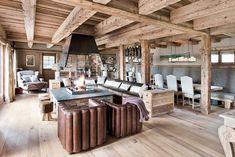 Le salon dans le chalet : cheminée centrale, fauteuils en cuir, chaises, chauffeuse méridienne, pouf...