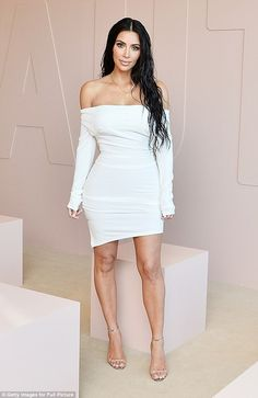 Slinky: Kim Kardashian posed wearing a white off-the-shoulder Vivienne Westwood dress for the launch of her KKW beauty collection on Tuesday night