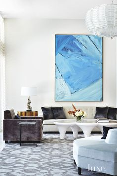 6: A Modern White Living Room in Miami Beach, FL  A coffee table from Scala Luxury in Los Angeles joins the designers' custom sofa and club chair to form an artful vignette in the living room beneath a painting by the owner.