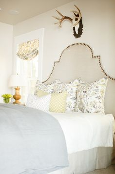 source: Caitlin Creer Interiors Arched linen upholstered headboard with nailhead trim. Bed layered with gray and yellow floral pillows, a yellow and white geometric pillow and small gray and white geometric pillow. Home Bedroom, Bedroom Decor, Master Bedroom, Bedroom Colors, Light Bedroom, Bedroom Interiors, Basement Bedrooms, Yellow And Gray Bedding, Yellow Walls
