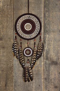 Brown color dream catcher. This is my authors dreamcatcher. Decorated with beautiful pheasant feathers.The dense woven web inside the willow hoop